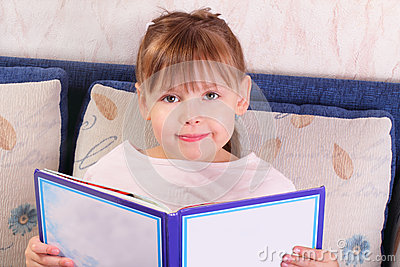 Pretty little girl sitting with book