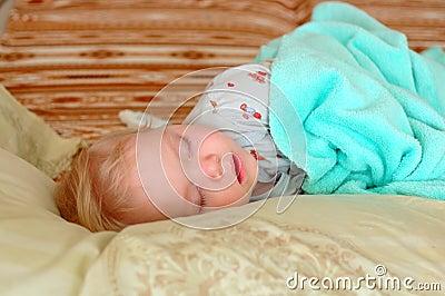 Pretty little girl sleep on big pillows.