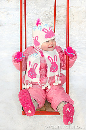 Pretty little girl on winter child s playground.