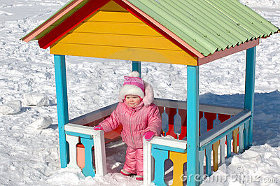 Pretty little girl and winter playground.