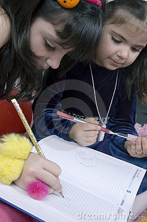 Pretty little girls playing with pencils
