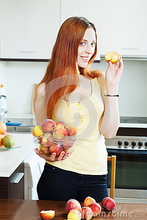 Pretty long-haired woman holding peaches