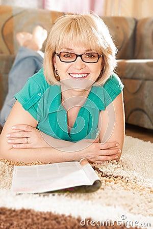 Pretty mature lady reading magazine on carpet stock photos image