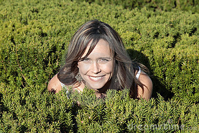 Pretty mother crouching in bushes