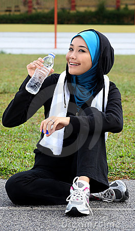 A pretty muslim woman athlete resting while drink