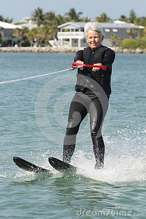 Free Pretty Older Lady Water Skiing By Nice House. Royalty Free Stock Photography - 52174217
