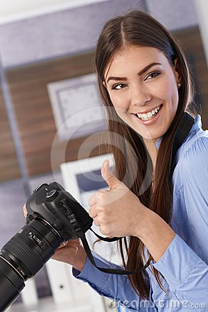 Pretty photographer giving thumb up