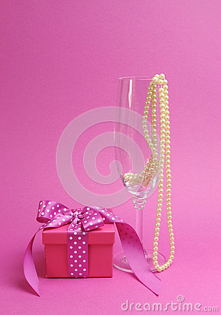 Pretty pink and feminine gift with polka dot pink ribbon and a champagne glass with pearls