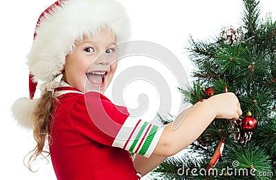 Pretty preschool child decorating Christmas tree