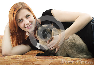 Pretty red-haired girl with a cat lying on the sofa