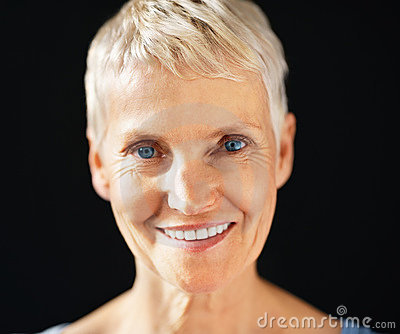 Pretty senior lady smiling over black background