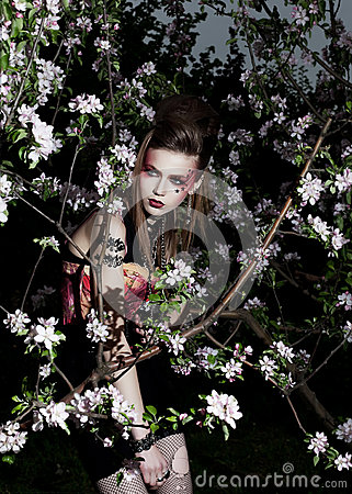 Pretty sensual girl in a garden. Creative makeup