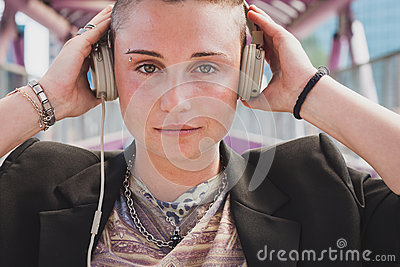 Pretty short hair girl listening to music on a bridge Stock Photo