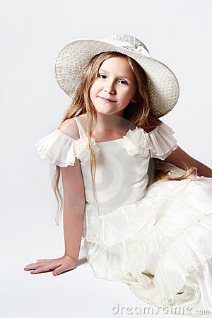 Pretty smiling child girl in white dress and hat