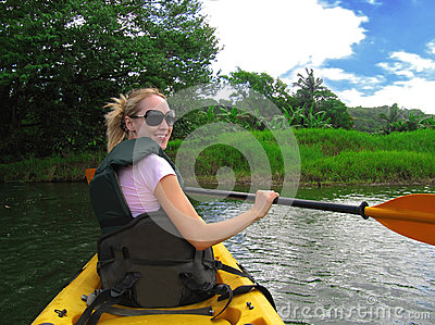 Pretty smiling girl is kayaking