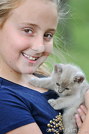 Pretty smiling happy girl with new pet kitten
