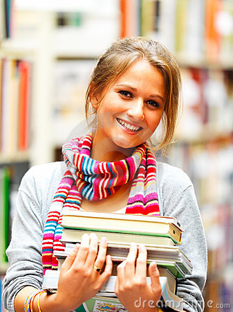 Pretty smiling lady holding books in library