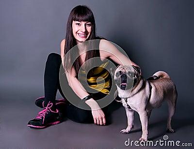 Pretty sport girl with pug dog in studio