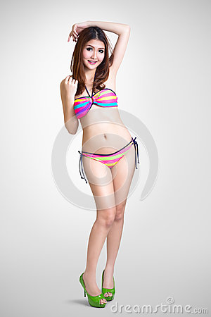 Pretty swimsuit fashion young asian woman posing on grey backgro