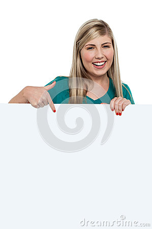 Pretty teen girl indicating downwards over ad board