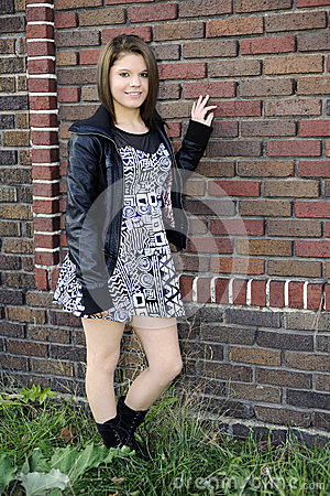 Pretty Teen Standing by a Brick Wall