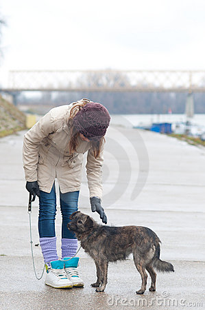 Pretty teenage girl with dog on cloudy winter day