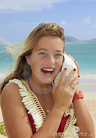 Pretty teenage girl listening to a seashell