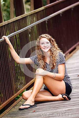 Pretty Teenage Girl Sitting on a Bridge