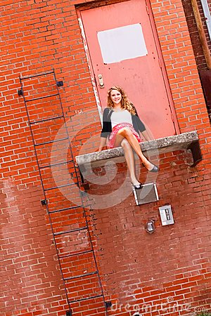 Pretty Teenage Girl Sitting on a Ledge
