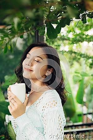 Free Pretty Vietnamese Woman Enjoying Her Morning Coffee On A Veranda Stock Photography - 96809942