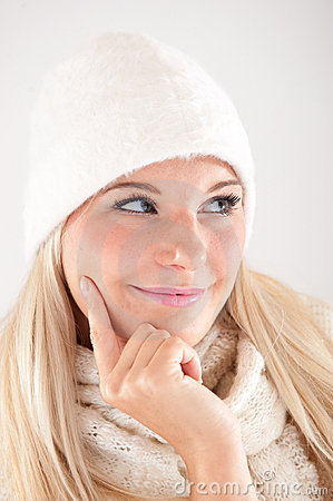 Pretty winter girl in white hat and scarf