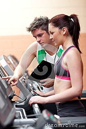 Pretty woman athlete standing on a running machine