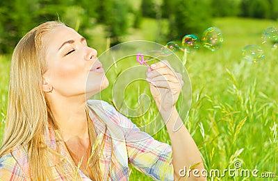 Pretty woman blowing soap bubbles in park