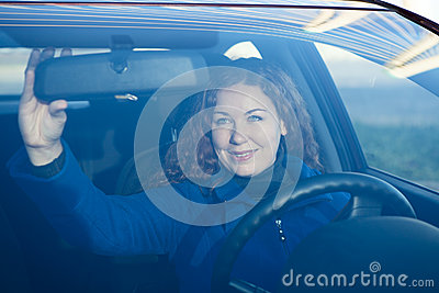 Pretty woman in car preparing to driving