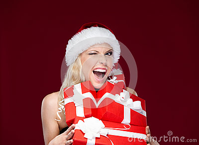 Pretty woman in Christmas cap holds presents