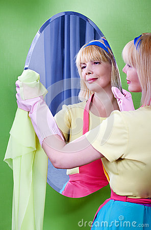 Pretty woman cleans mirror at home