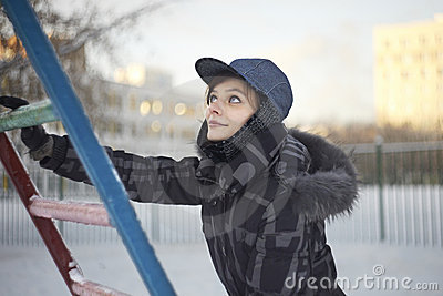 Pretty woman climbing on metallic ladder in winter