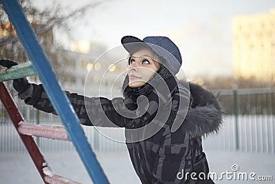Pretty woman climbing on metallic ladder in winter