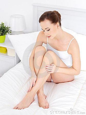 Pretty woman in dedroom touching beautiful legs