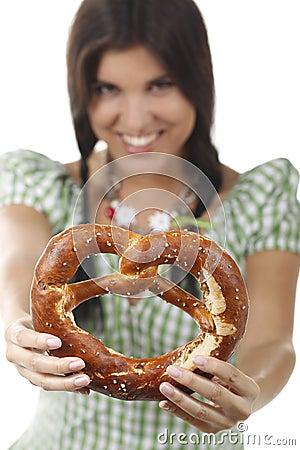 Pretty woman with dirndl and pretzel