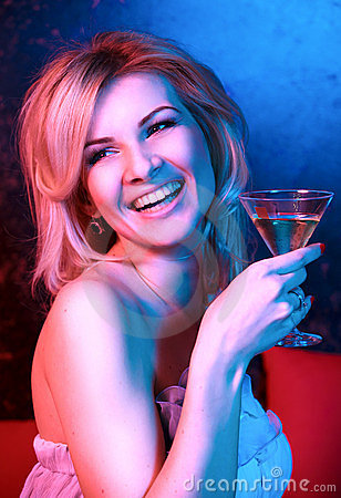 Pretty woman drinking cocktail in nightclub