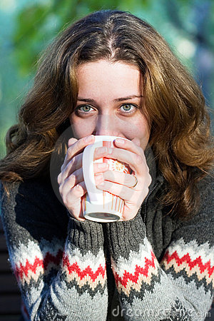Pretty woman drinking a coffee outdoors