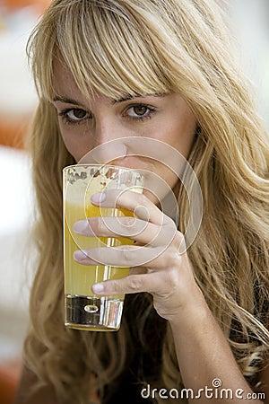 Pretty woman drinking a glass of orange juice