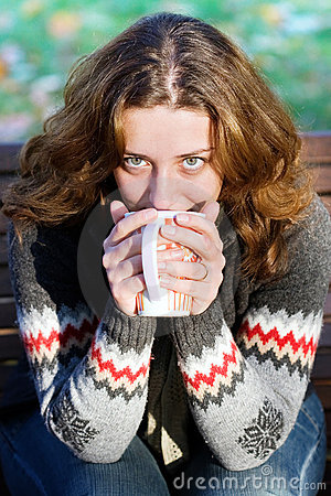 Pretty woman drinking tea outdoors