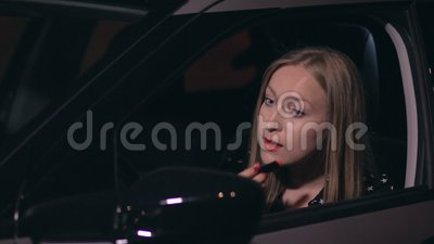 Pretty woman driver in a car doing makeup stock video