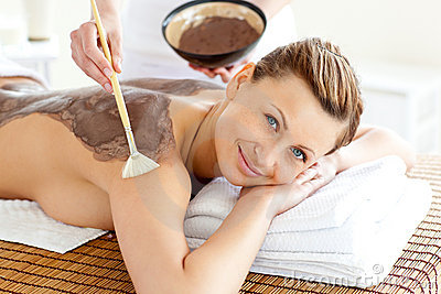 Pretty woman enjoying a beauty treatment with mud