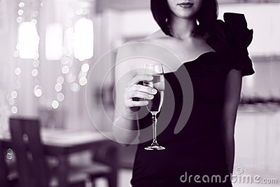 Pretty woman in glad rags, holding glass of drink