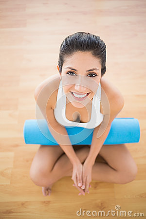 Pretty woman holding her exercise mat sitting and smiling at camera