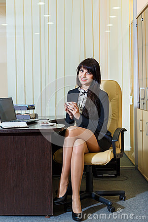 Free Pretty Woman In A Short Skirt Drinking Coffee In  Office Royalty Free Stock Image - 58938946