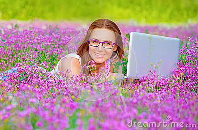 Pretty woman with laptop on floral field